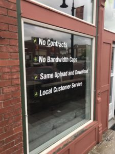 "Sign on Building that says ""No Contracts, No Bandwidth Caps, Same Upload and Download, Local Customer Service"""