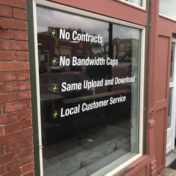 """Sign on Building that says """"No Contracts, No Bandwidth Caps, Same Upload and Download, Local Customer Service"""""""